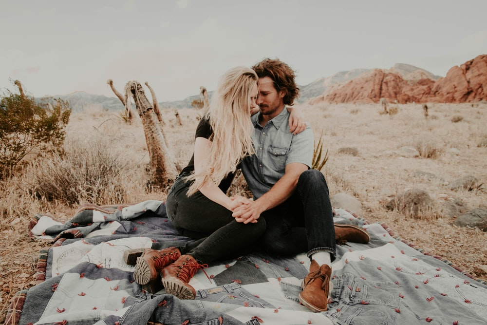 man and woman sitting on blanket while holding each other hands