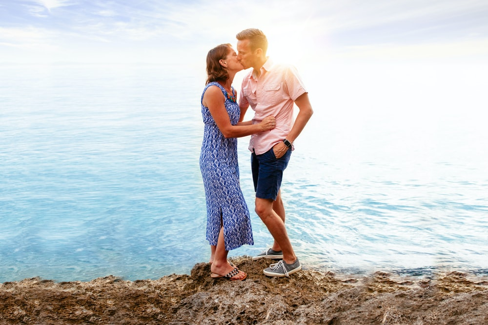 man and woman kissing near body of water