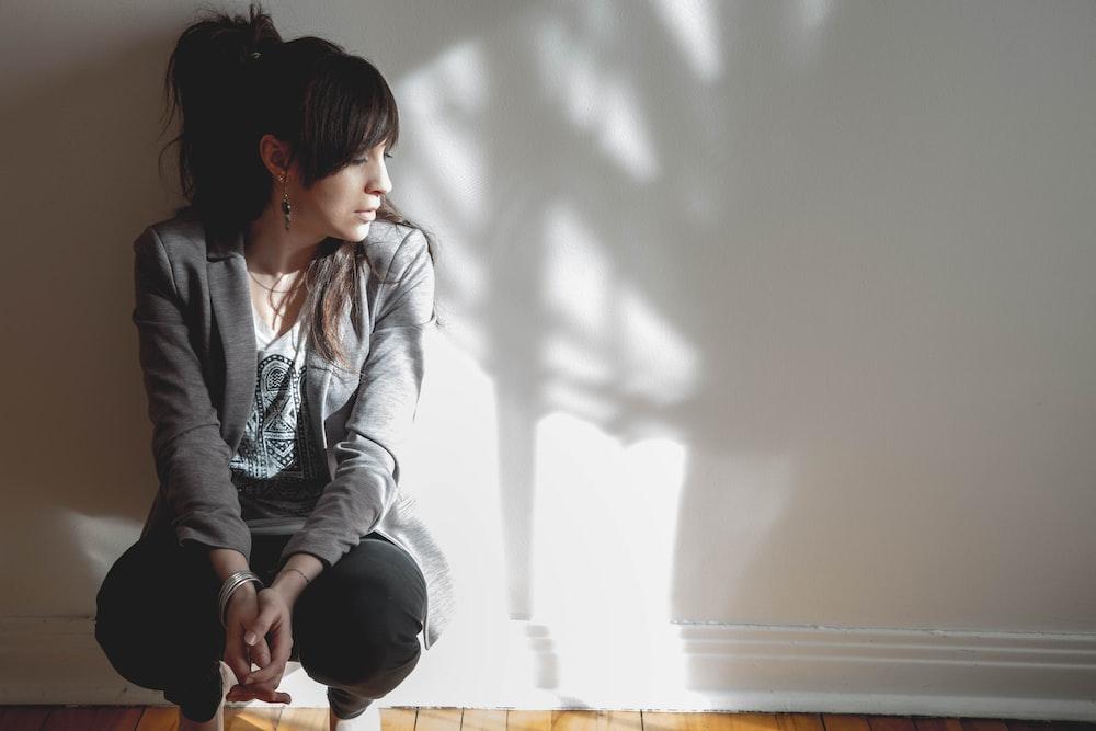 woman sitting beside white wall