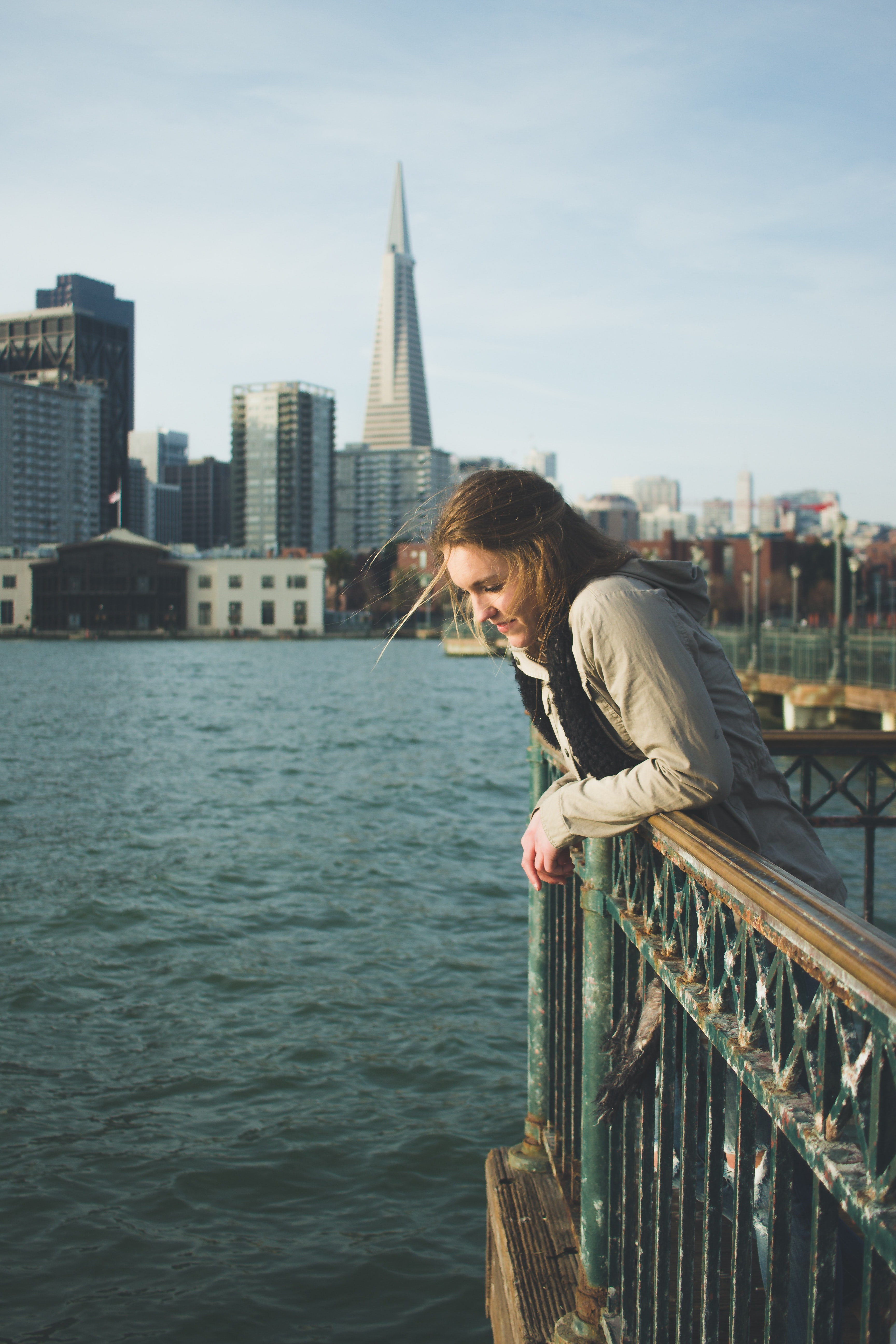 woman leaning on green steel fence
