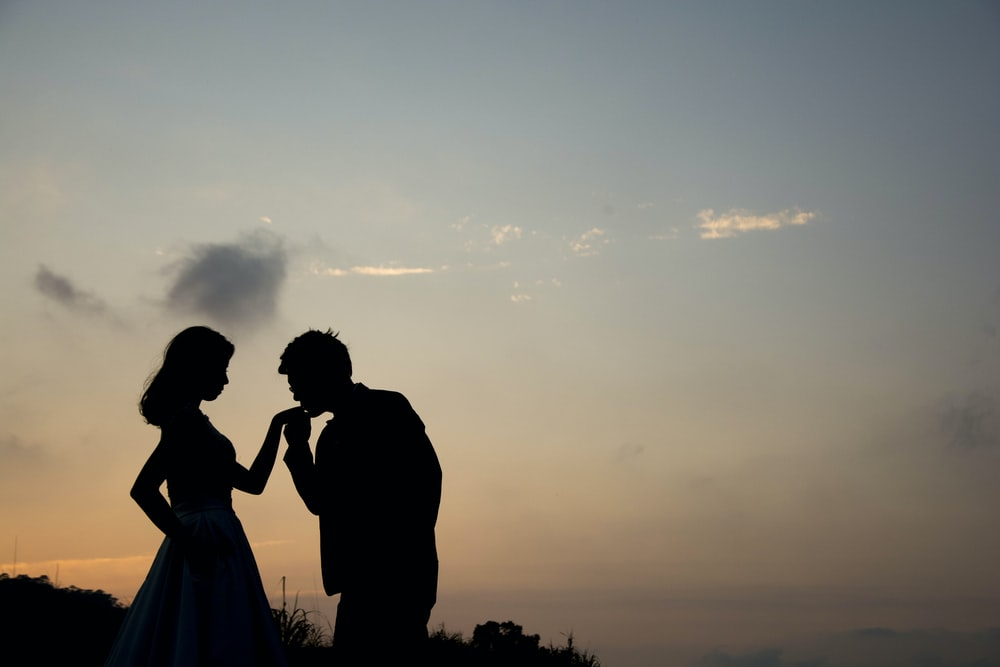 silhouette of man kissing hand of woman