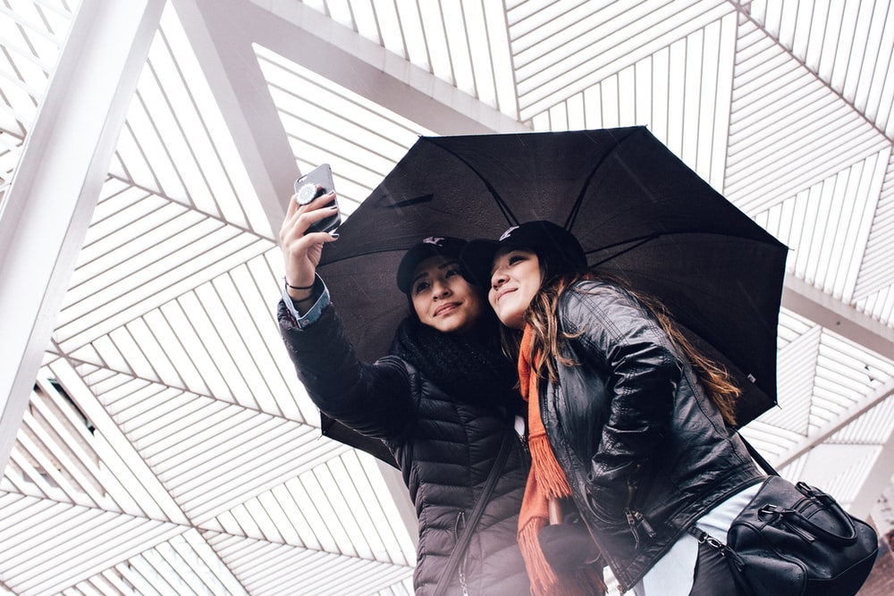 two women's using umbrella while taking selfie