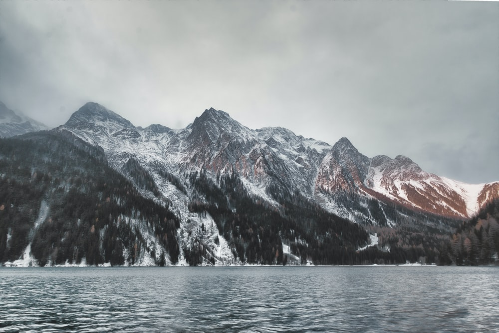 mountain covered with snow under gray clouds