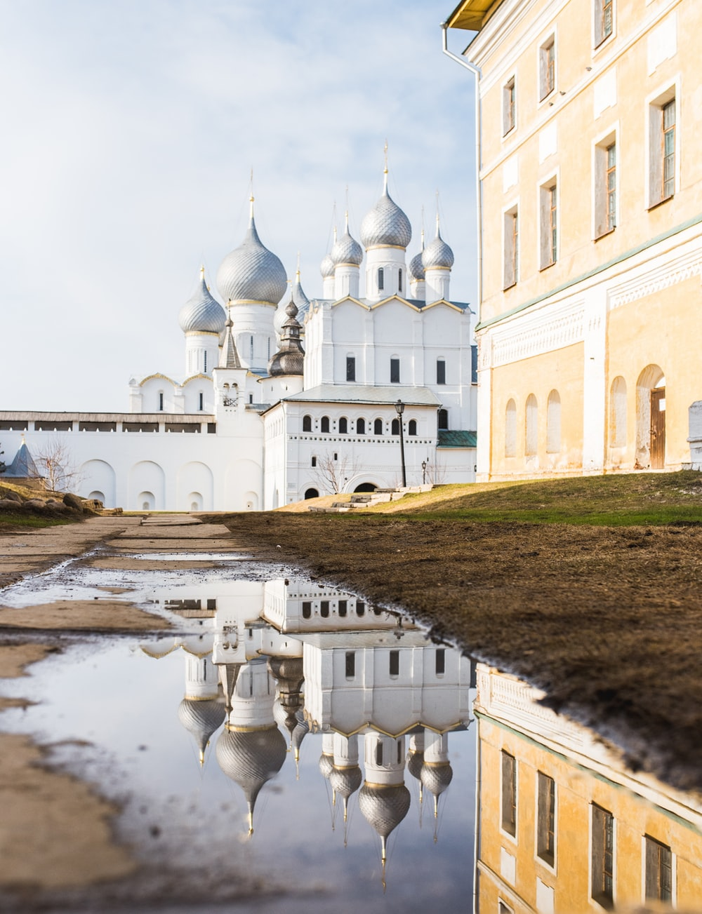 white mosque near the beige 3-storey building