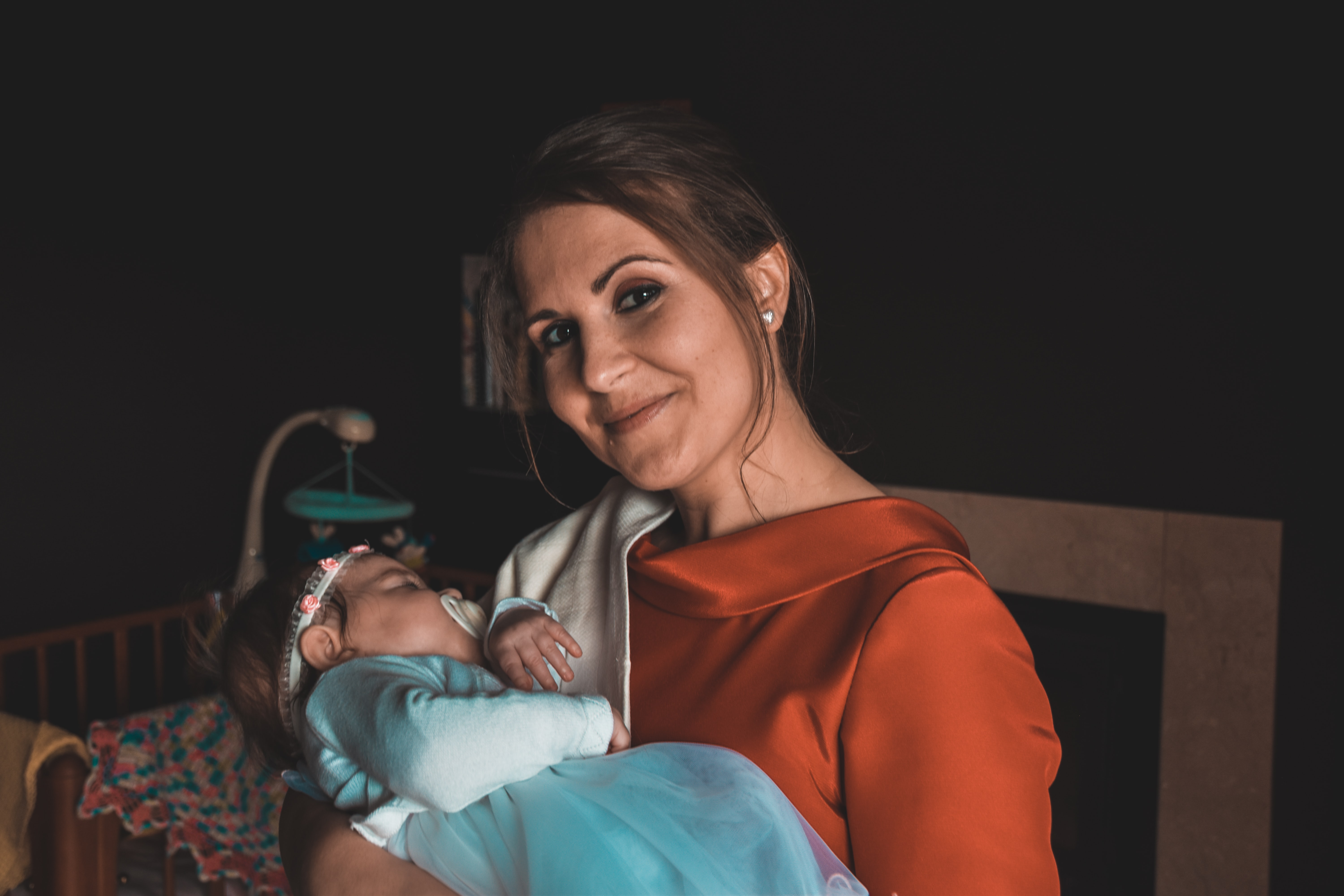 smiling woman carrying sleeping baby