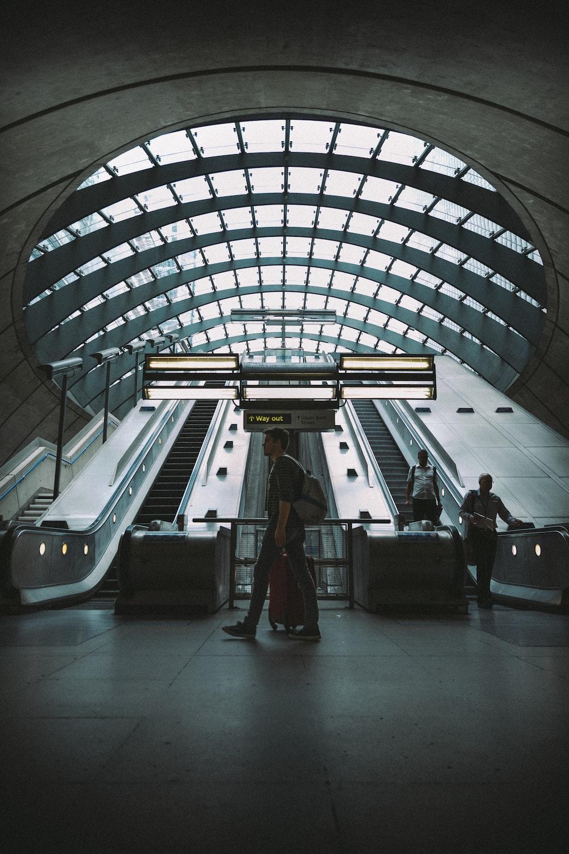 man walking near escalator and two men