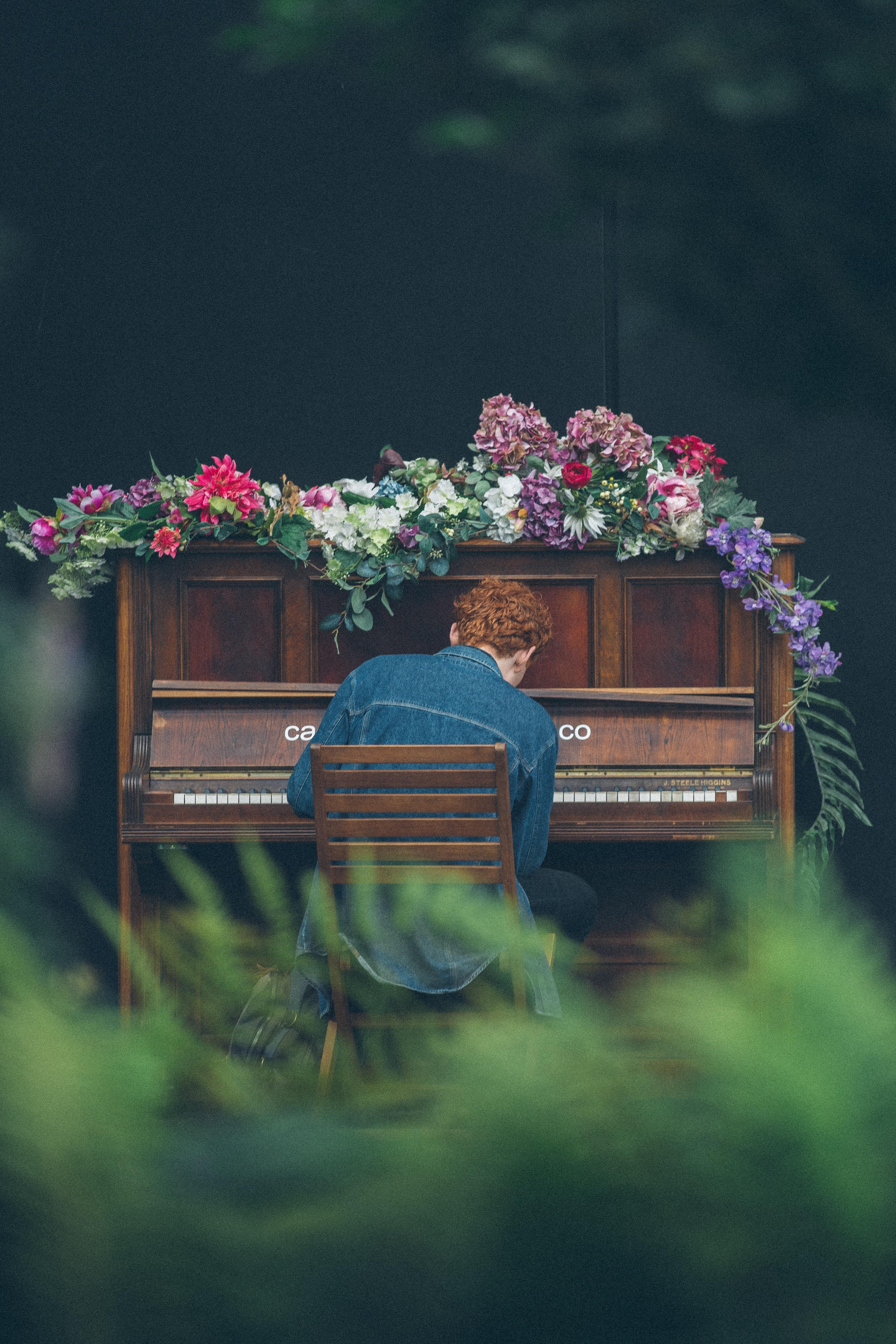 man playing upright piano