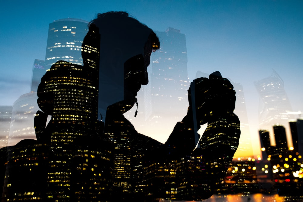 silhouette of man holding camera on glass window
