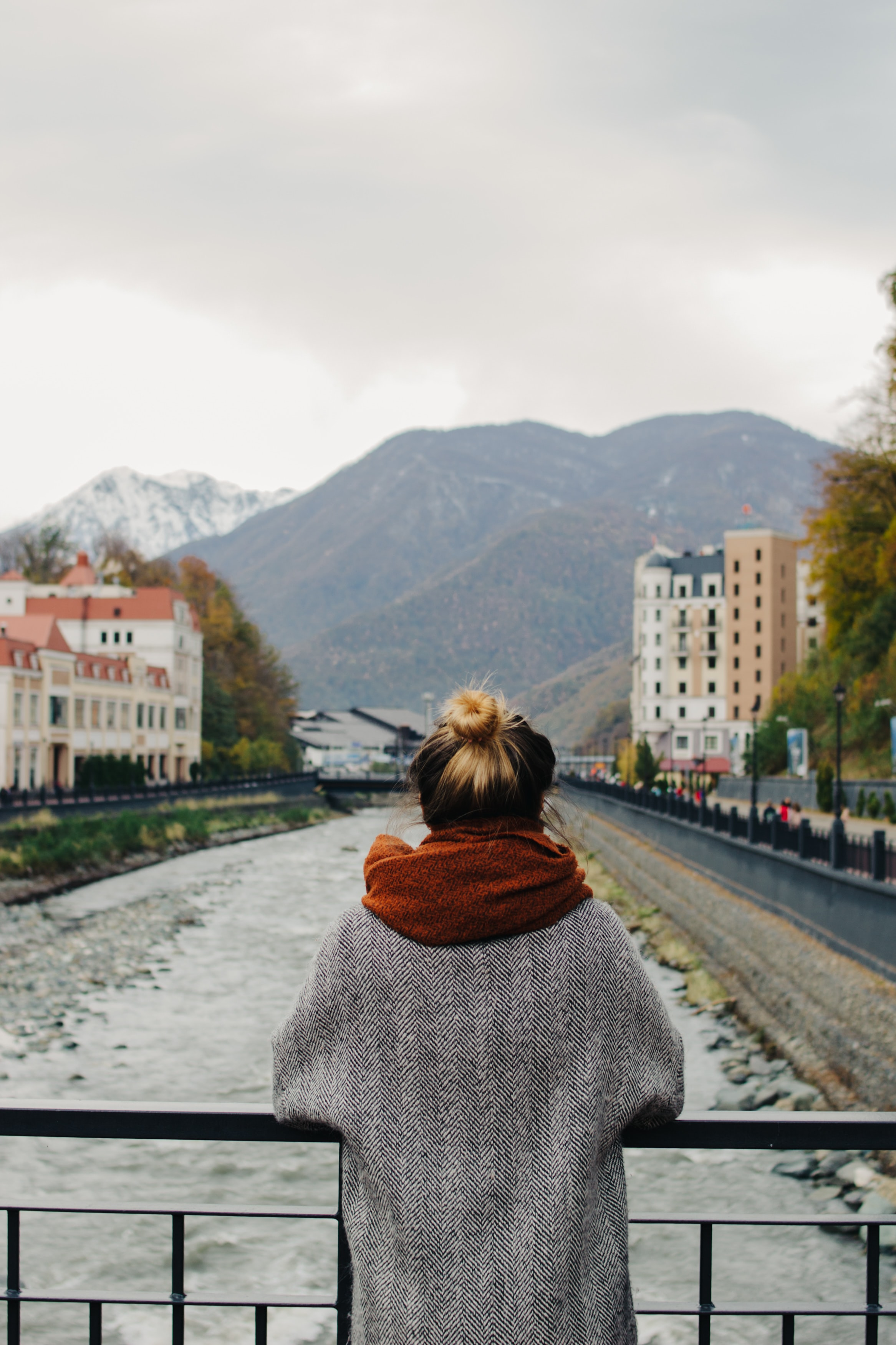 woman in gray coat leaning on metal bridge rail
