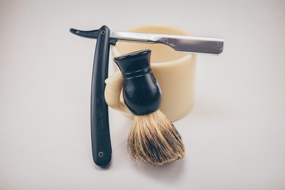 black straight razor beside beige ceramic mug and shaving cream brush