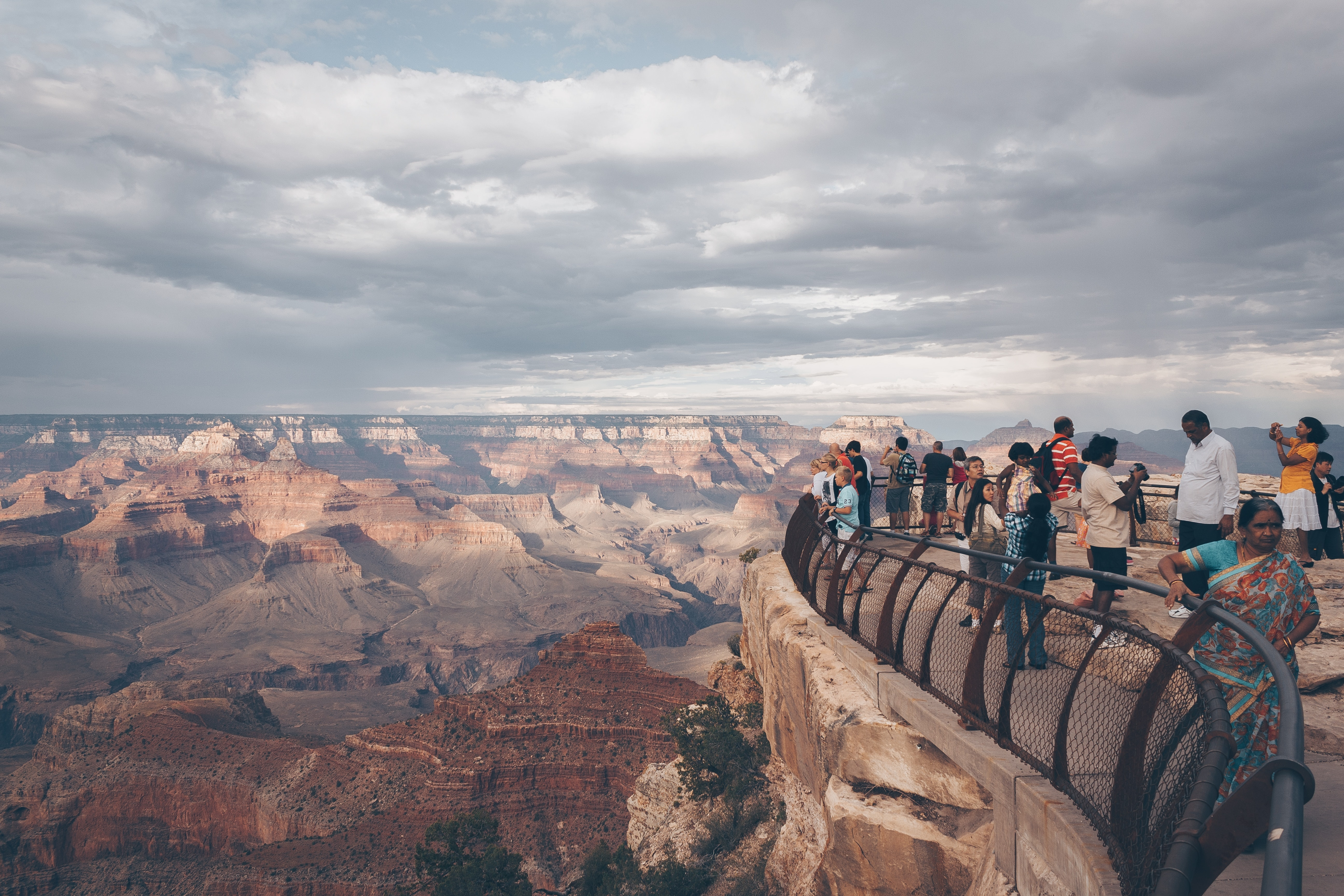 group of people standing at the top of cliff with railing