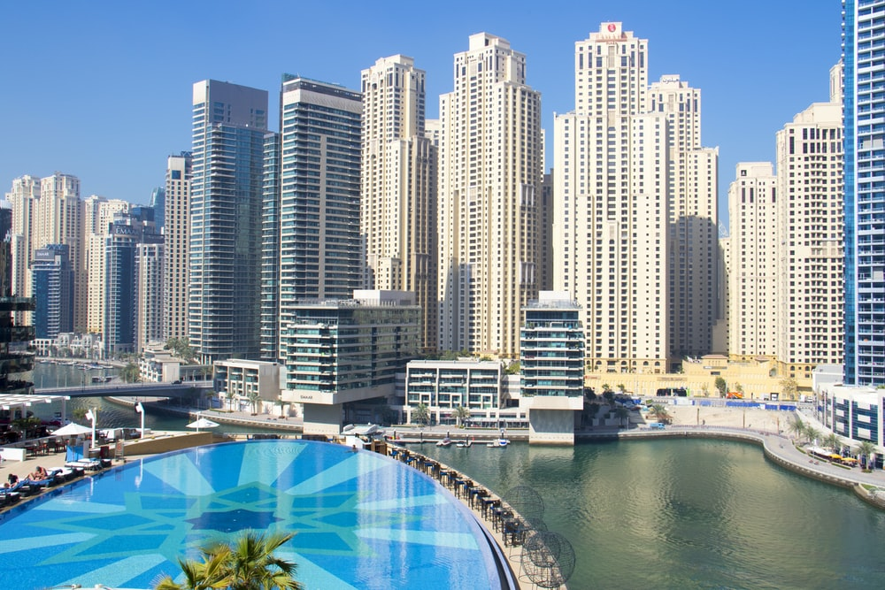 city buildings near in-ground pool during daytime