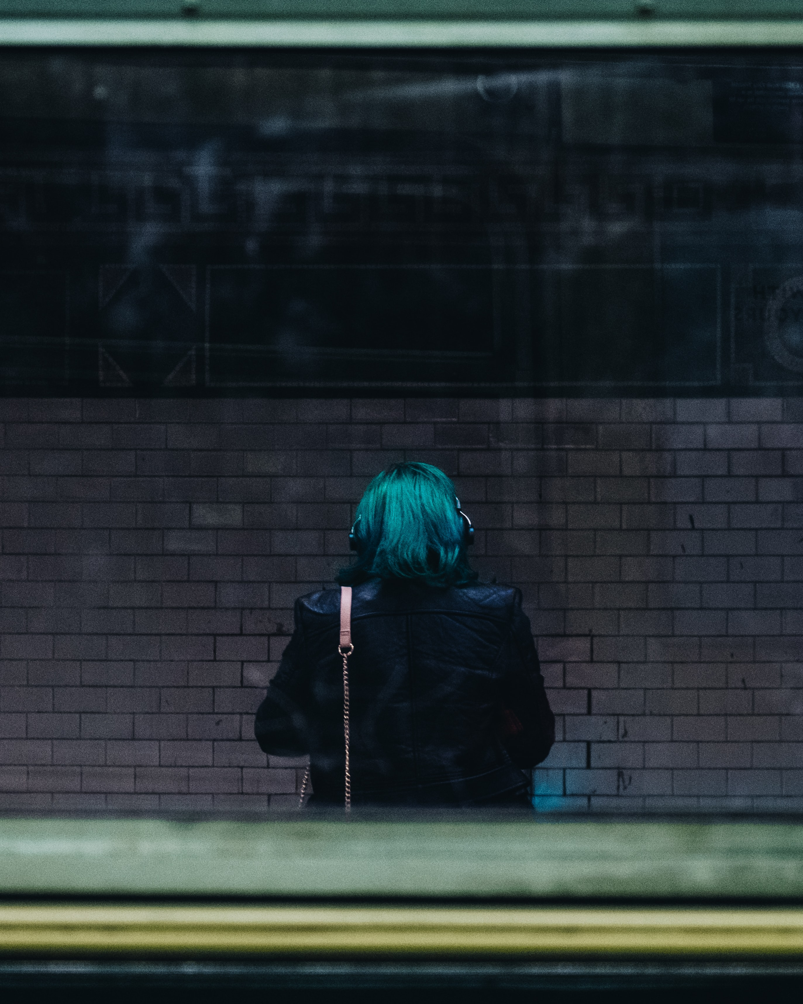 teal hair colored person standing behind glass panel