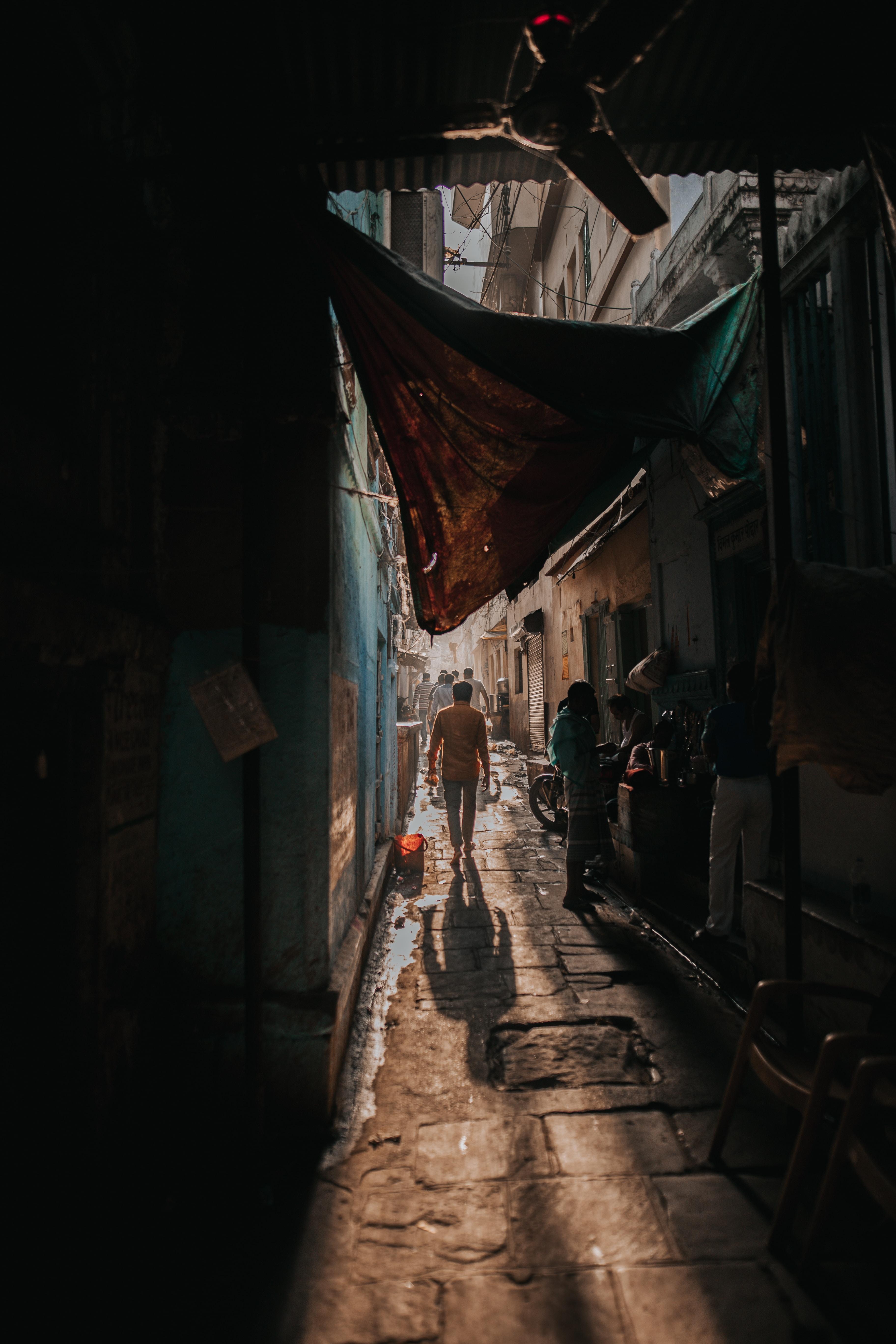 man walking on pathway between houses