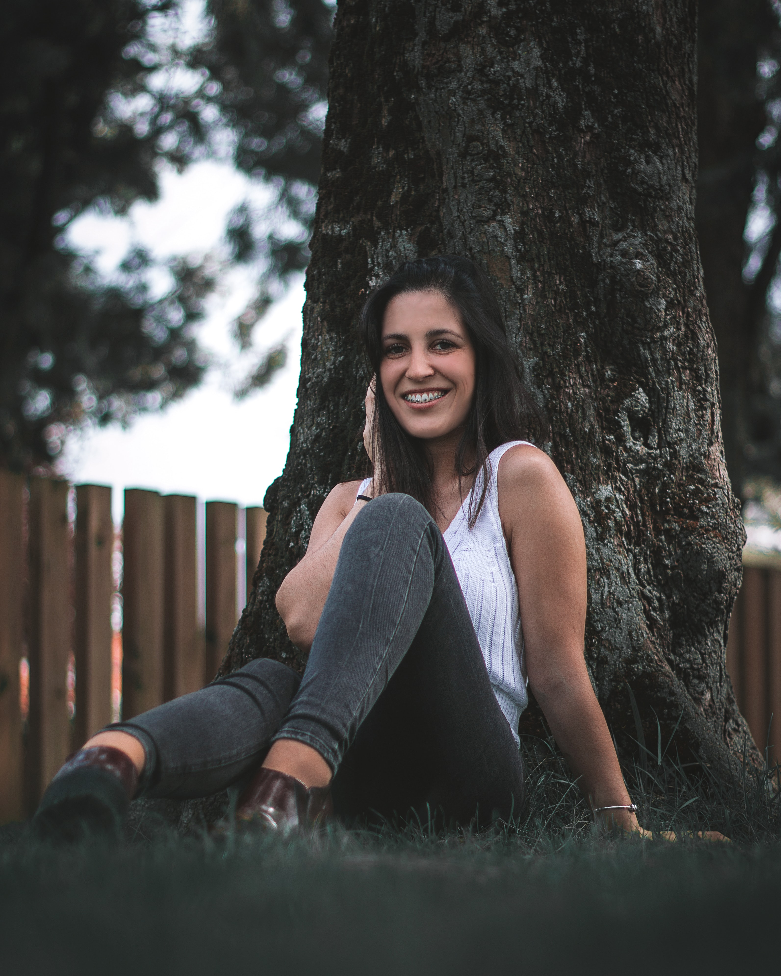 woman sitting on grass field while leaning on tree trunk