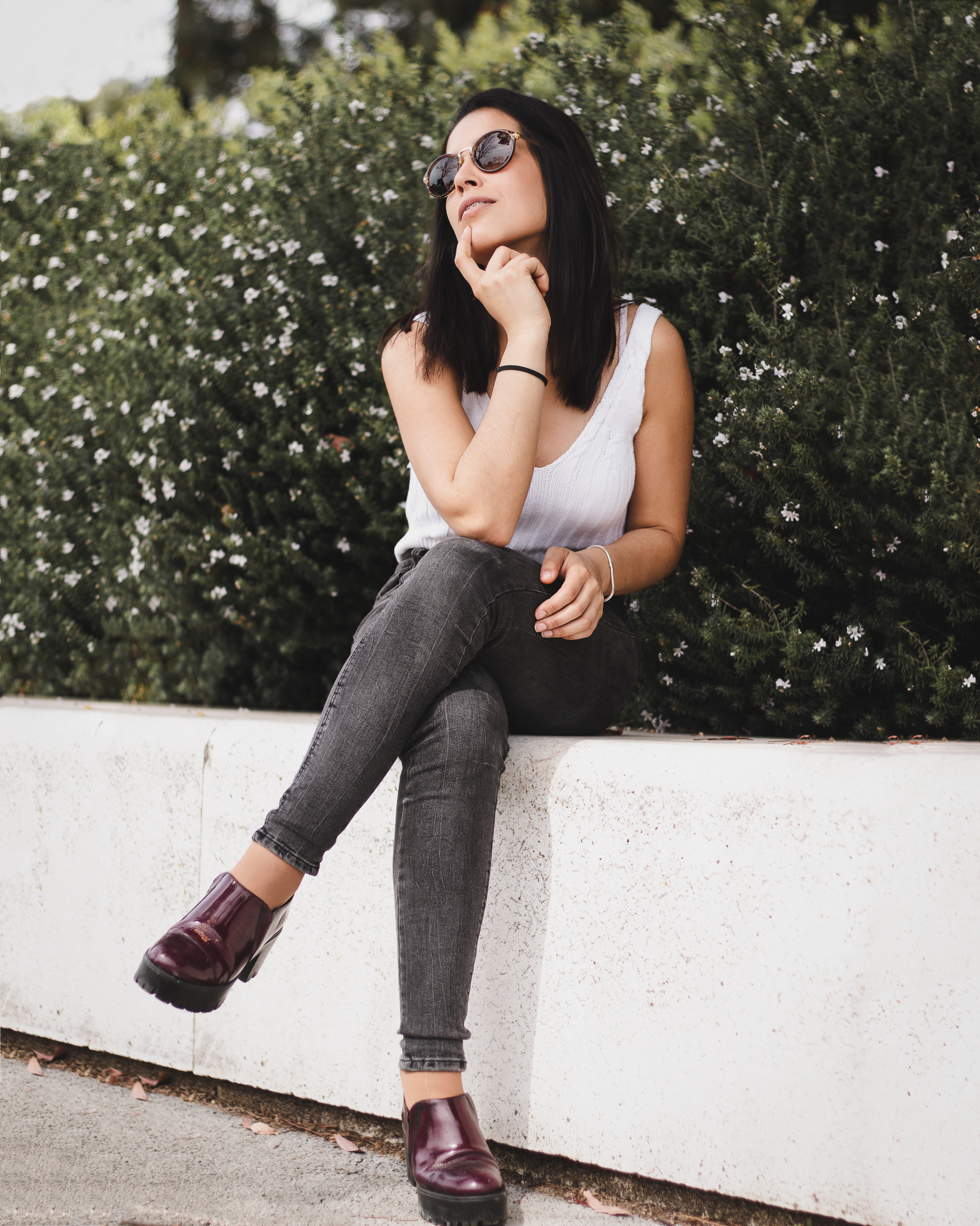 woman wearing tank top, skinny jeans, sunglasses outfit sat on concrete gutter