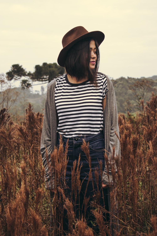 woman standing in brown grass field