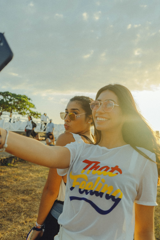 women taking photo near beach at daytime