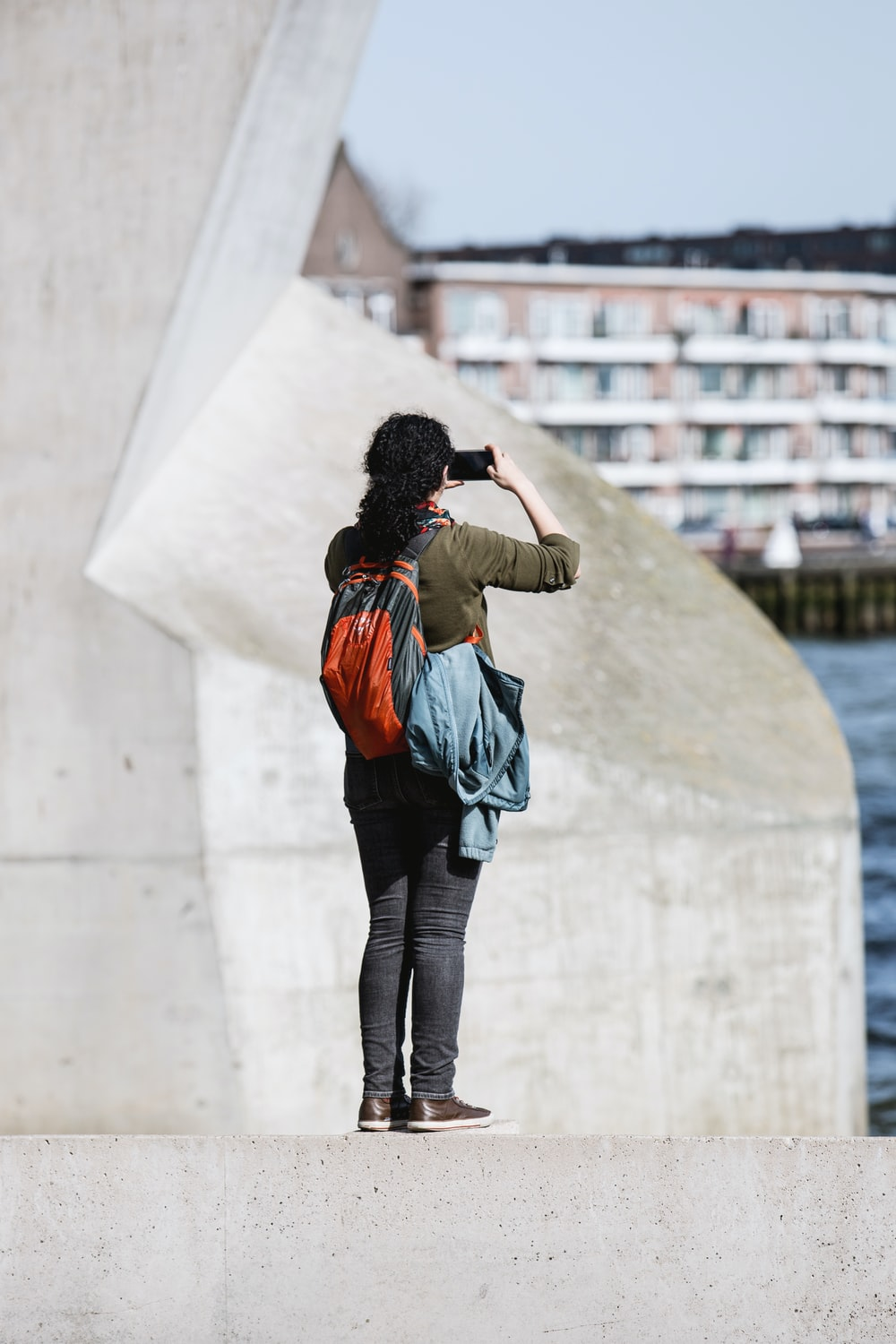 person standing on concrete edge holding up smartphone taking photo