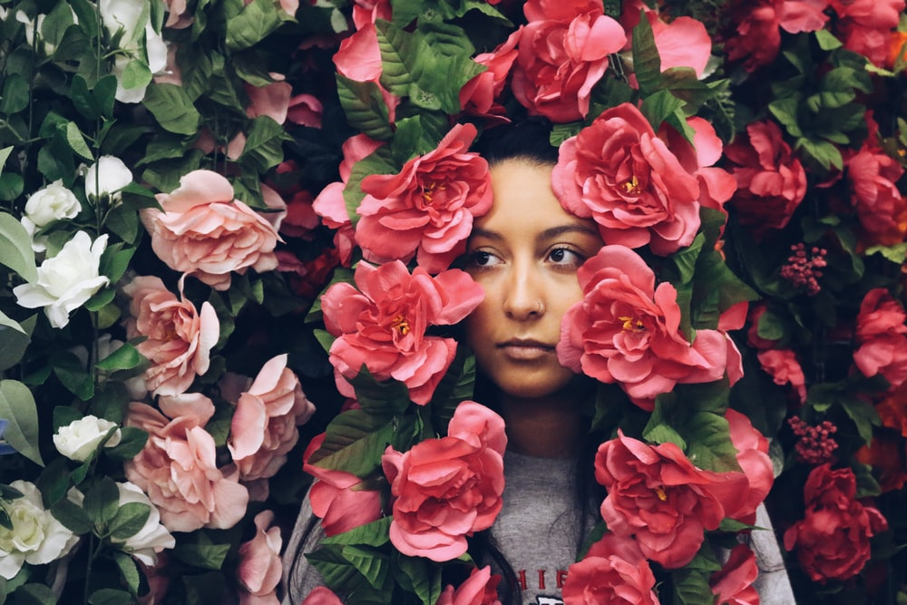 woman surrounded by red petaled flowers
