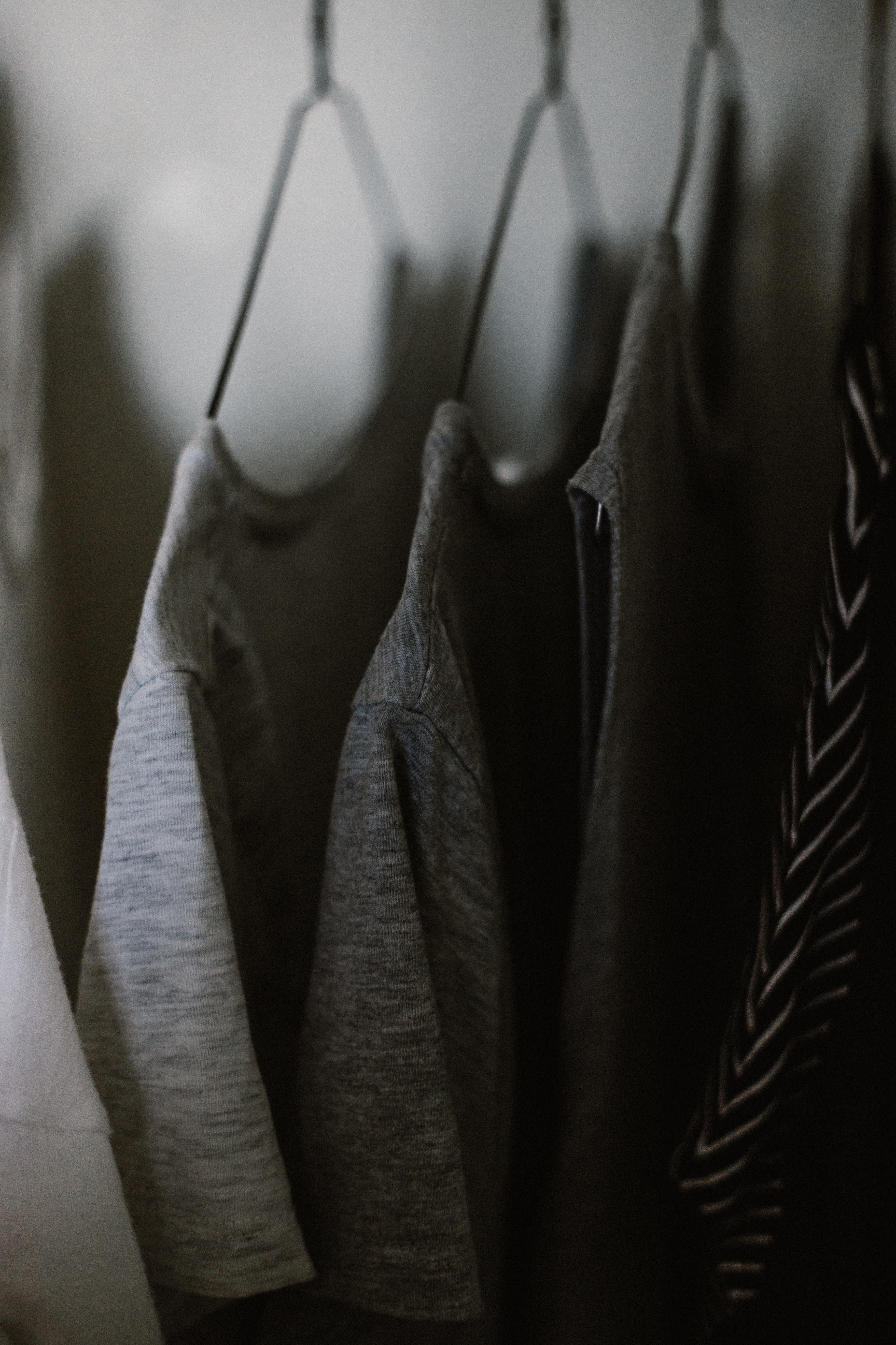 selective focus photography of hanged three gray tee shirts