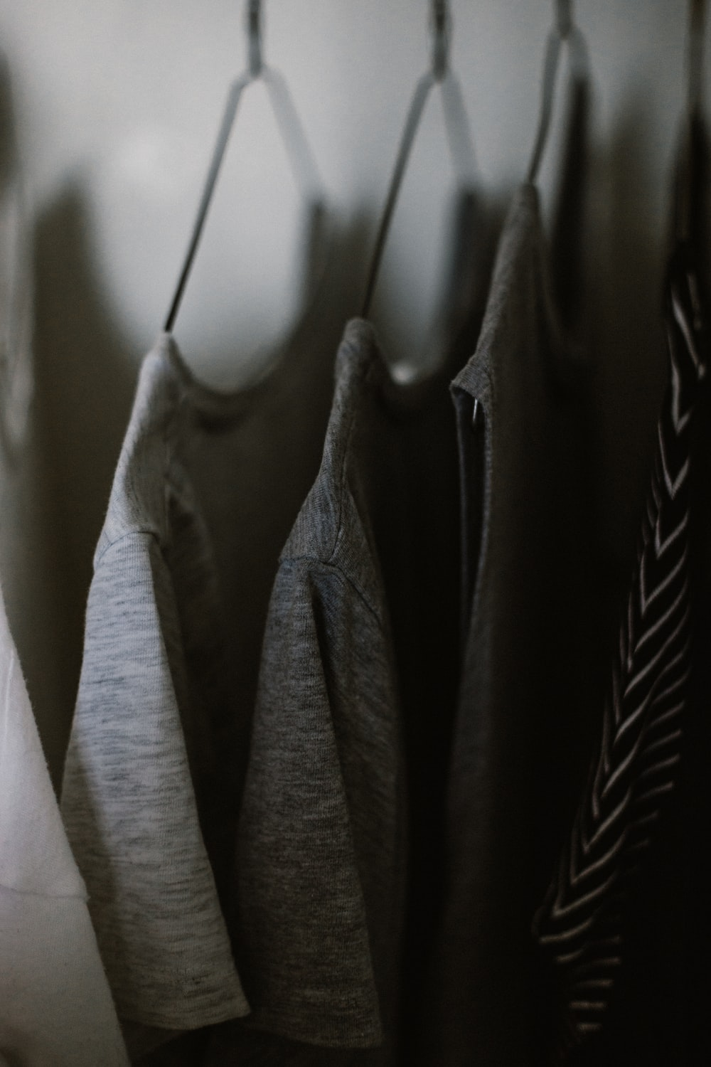 selective focus photography of hanged three gray tee shirts