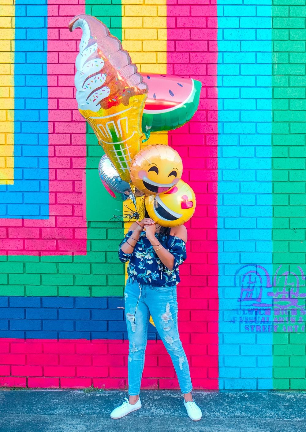 woman covering face with assorted ballons