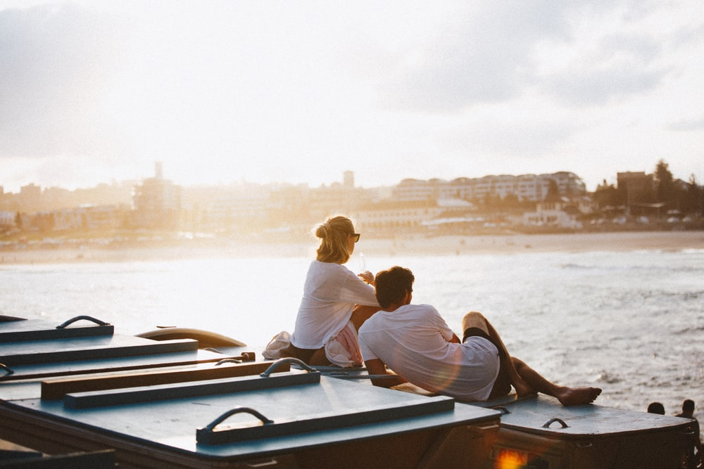 couple sitting on boat in front of body of water