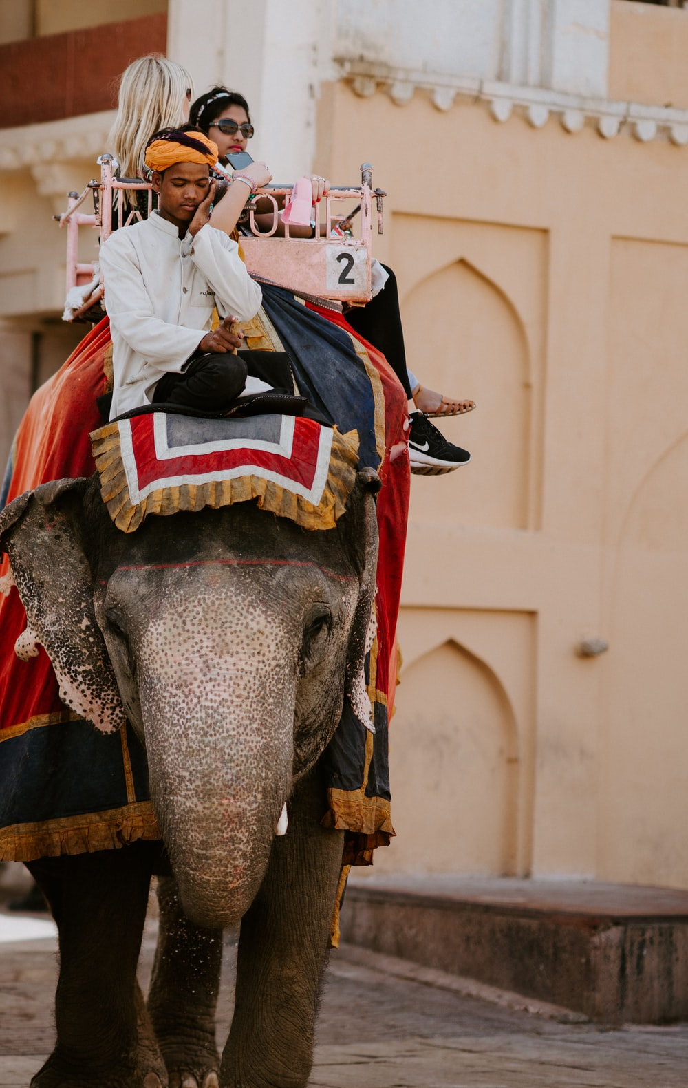 man and woman riding elephant