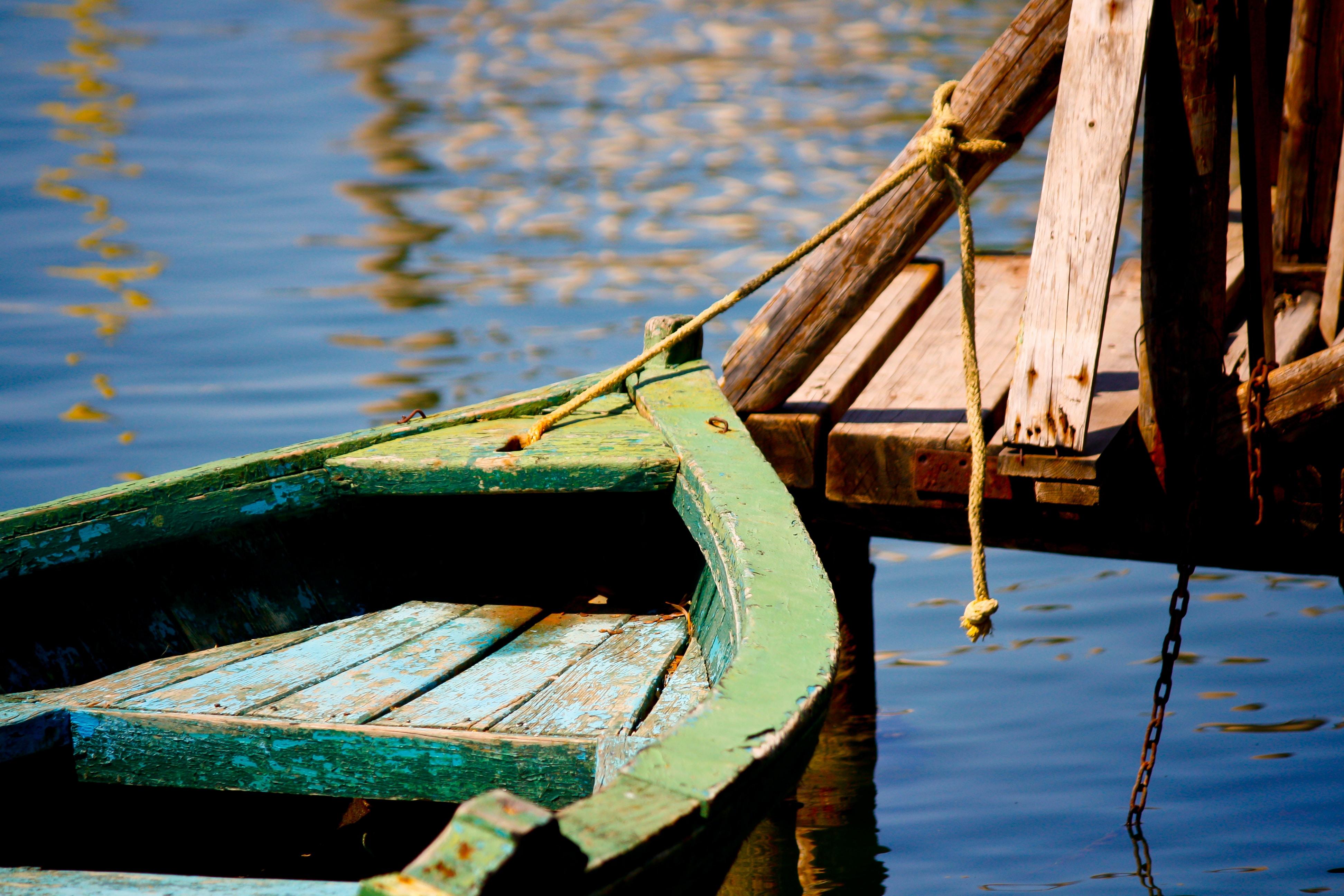 green wooden boat beside the docking pier