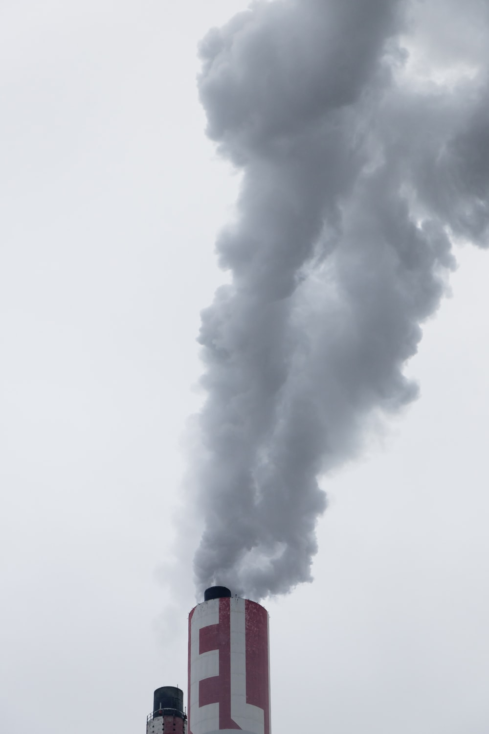 red factory chimney with smoke