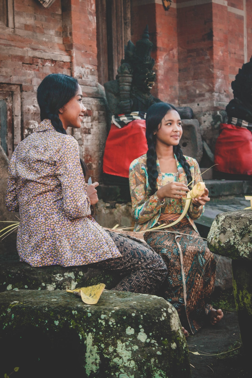 woman holding woven coconut leaf beside woman sitting while holding knife
