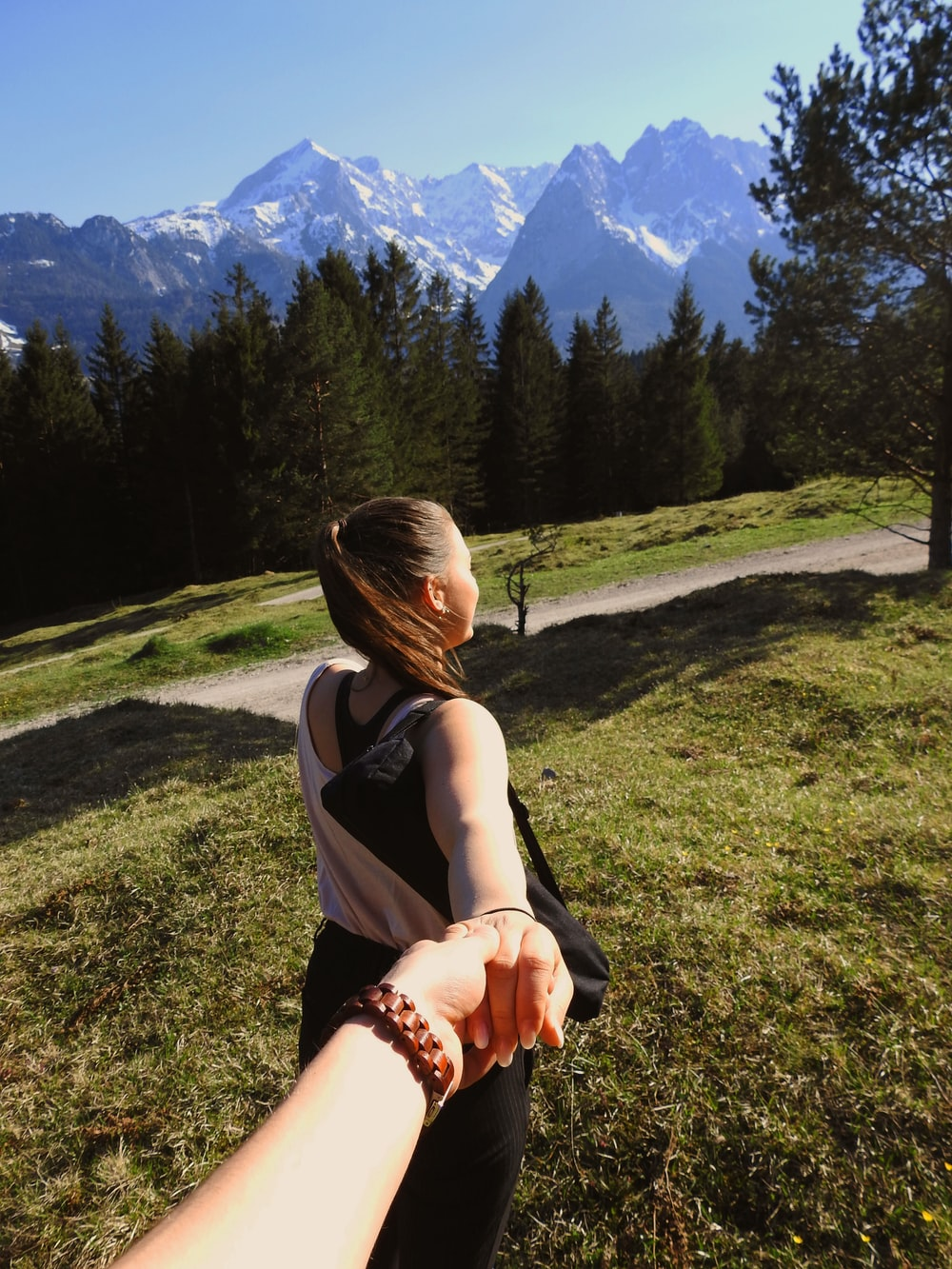 person holding woman hand standing near pine trees and mountain during daytime
