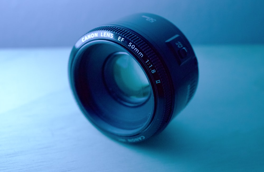 shallow focus photography of black Canon DSLR camera lens