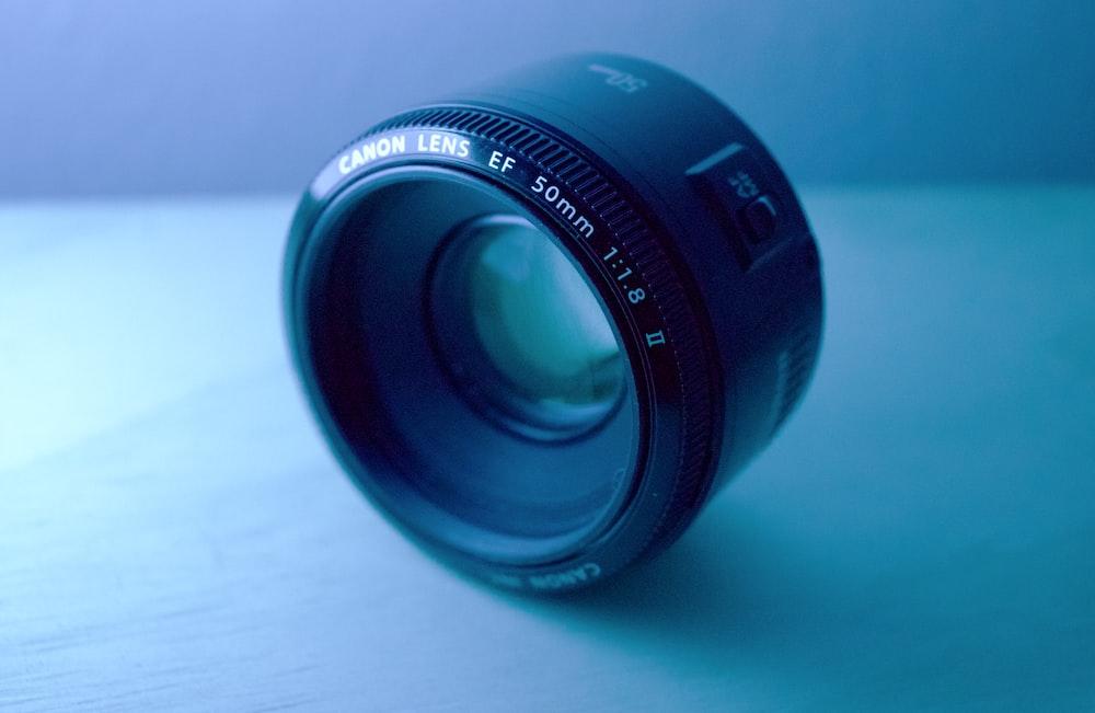 shallow focus photography of black Canon DSLR camera lens