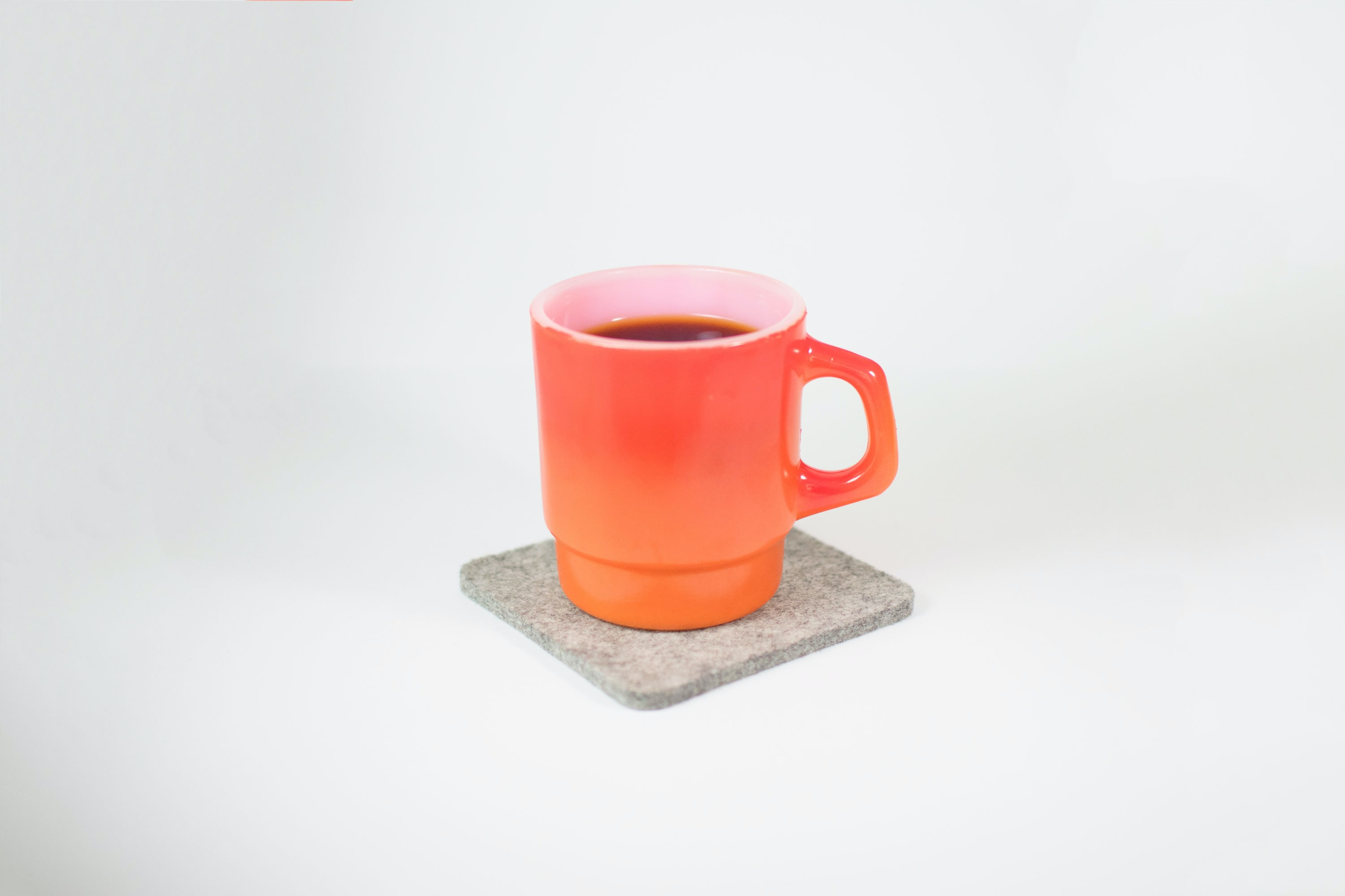 orange mug filled with black liquid