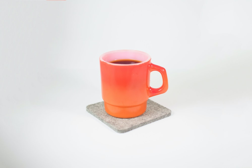 orange mug filled with black liquid