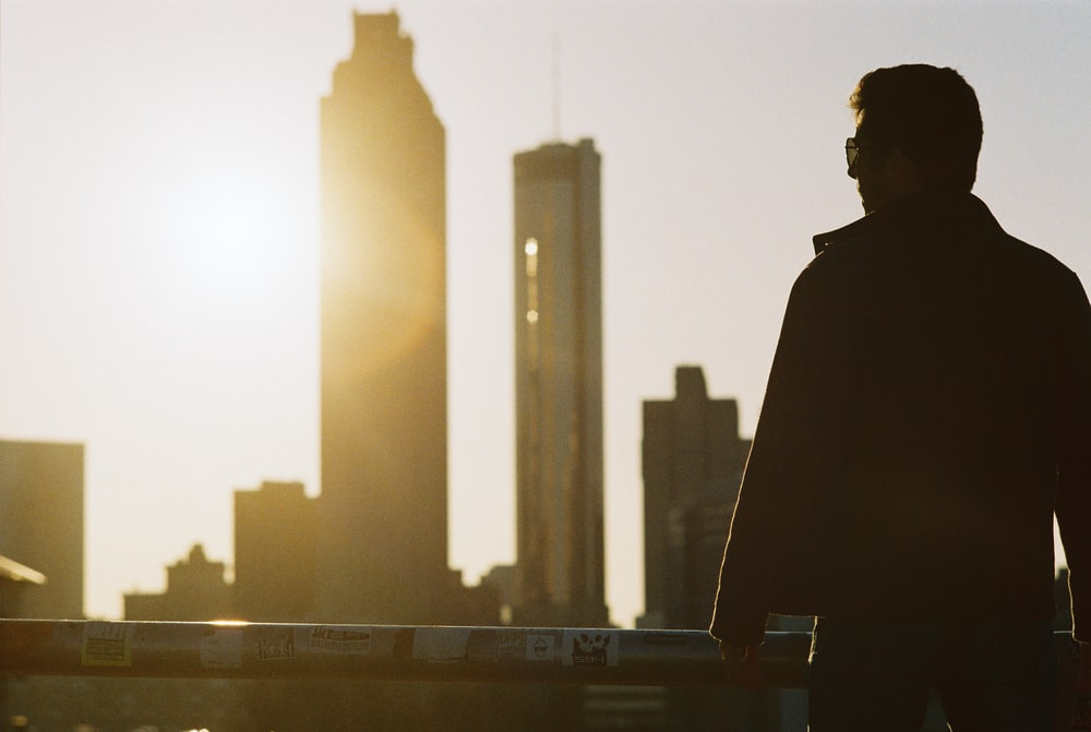 silhouette of man standing near railing