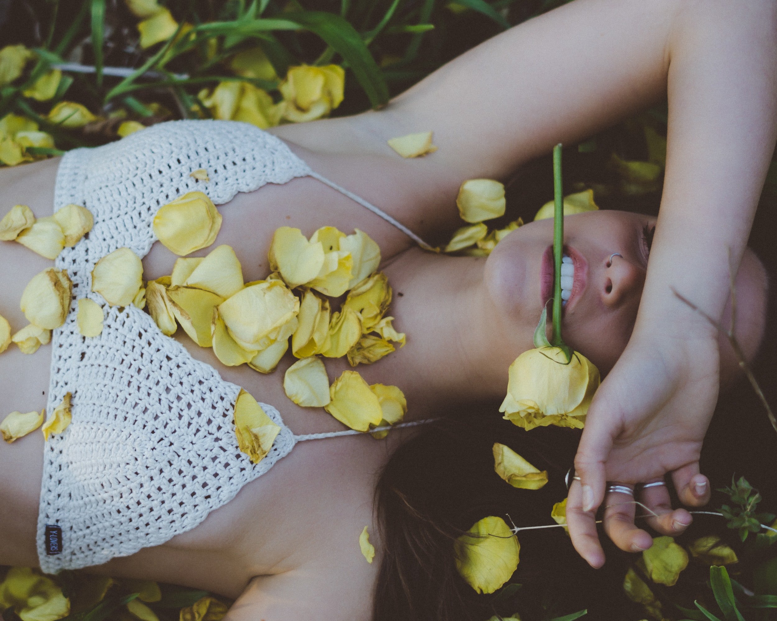 woman laying on plant with yellow flower on mouth