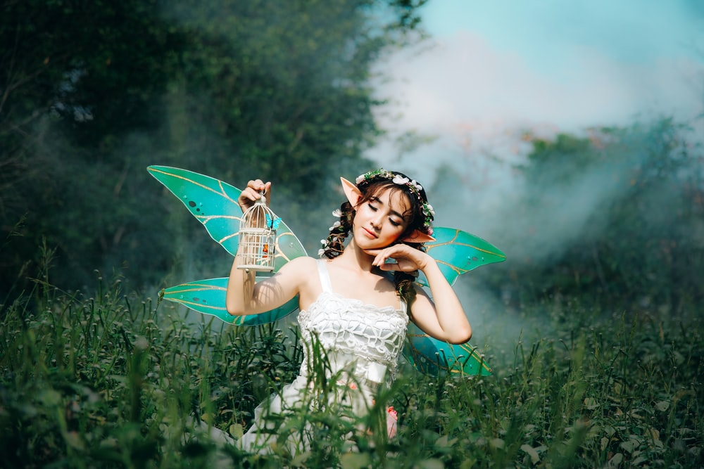 woman in white dress wearing green fairy wings