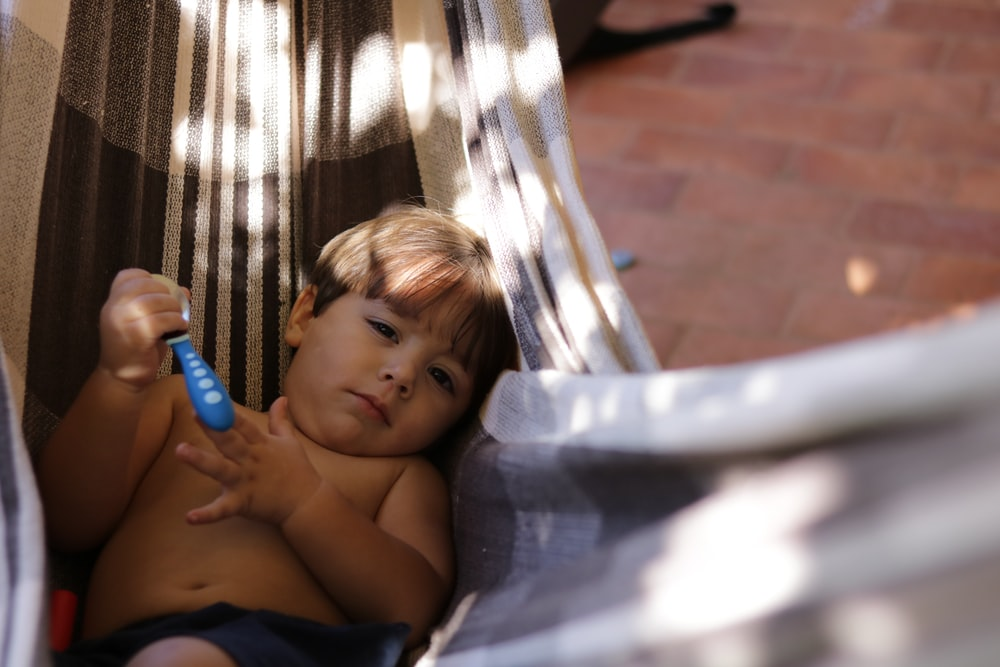 boy holding spoon lying in hammock