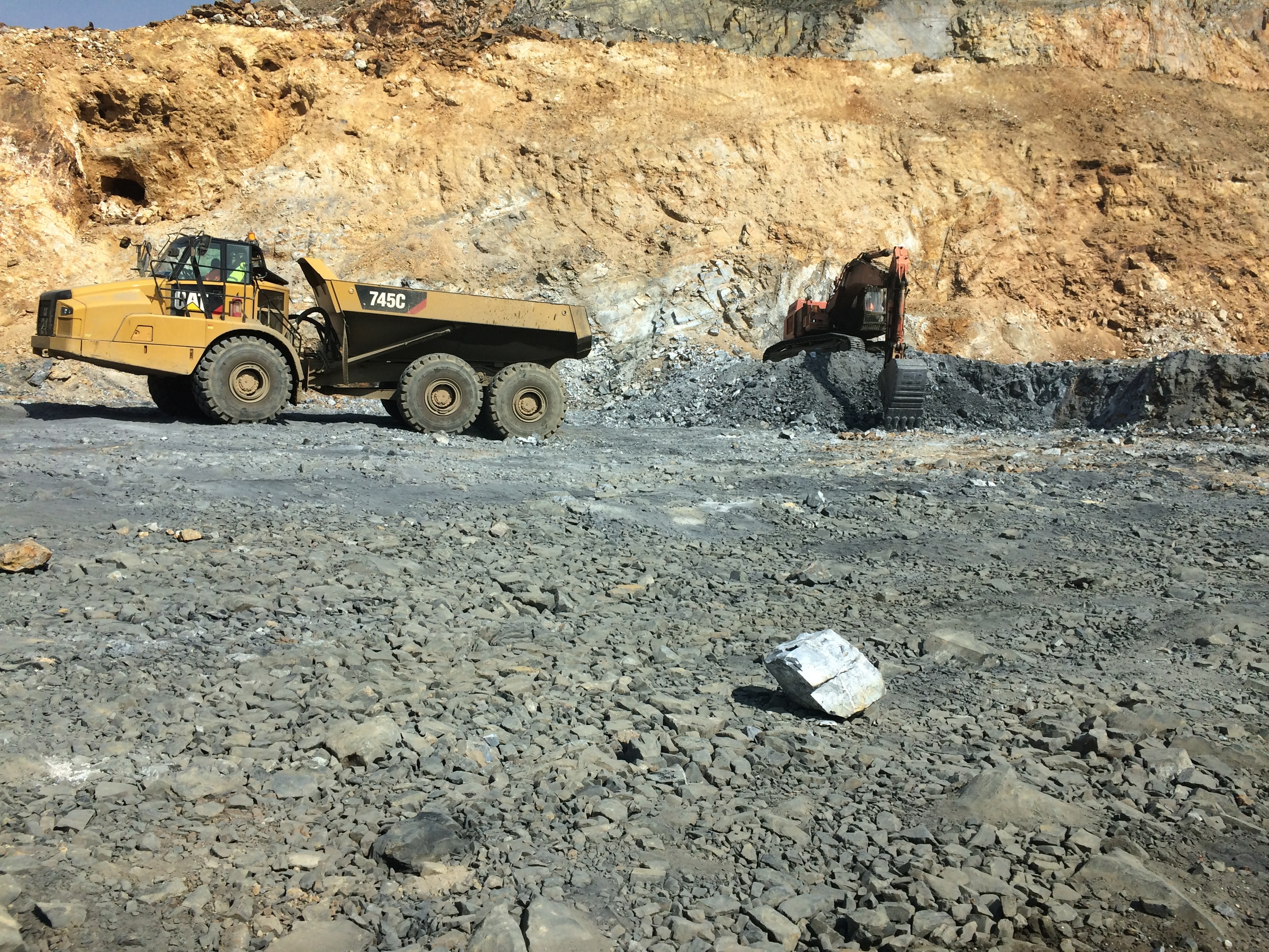 yellow heavy equipment filled with stone by back-hoe