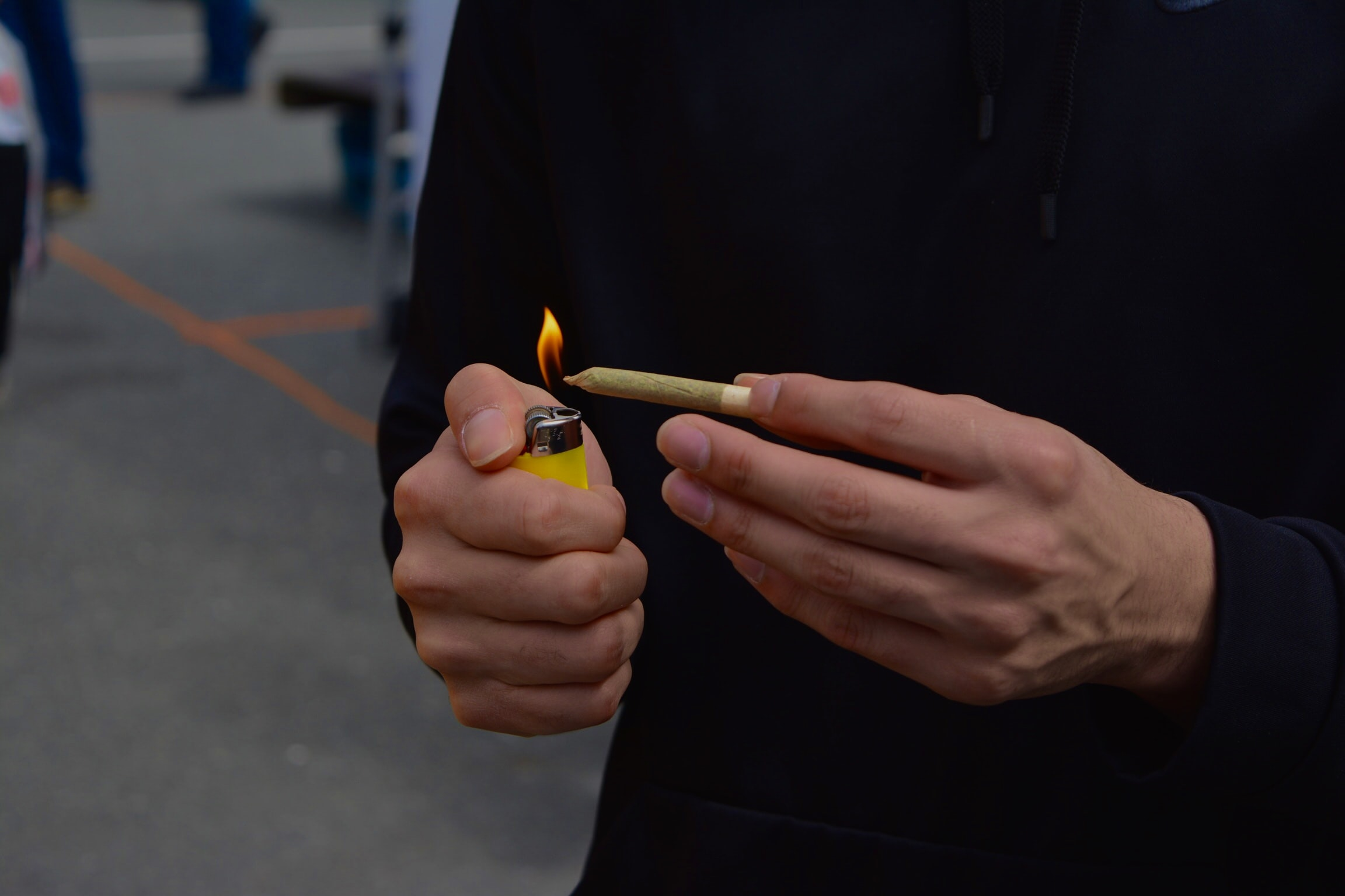 person holding blunt and lighter