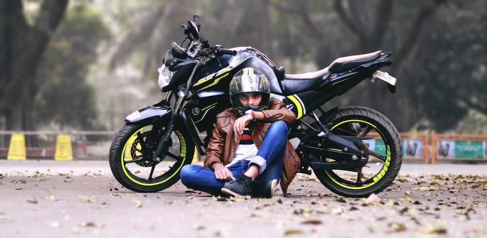 man lying beside black motorcycle