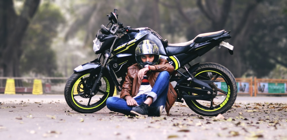 man lying beside black motorcycle