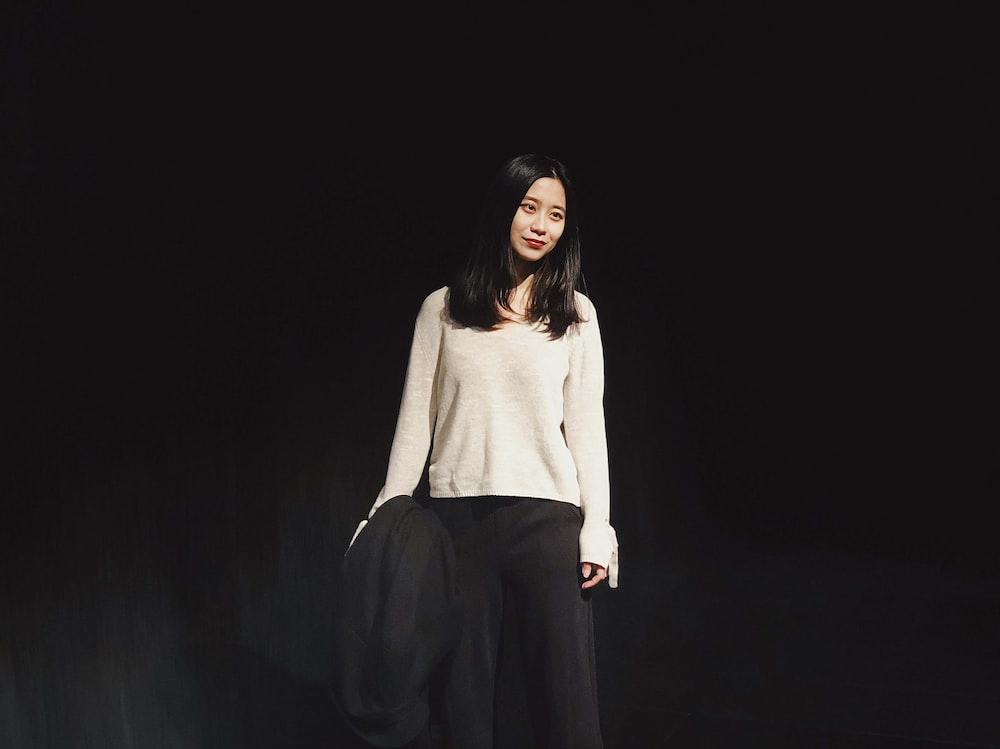 woman standing behind black background