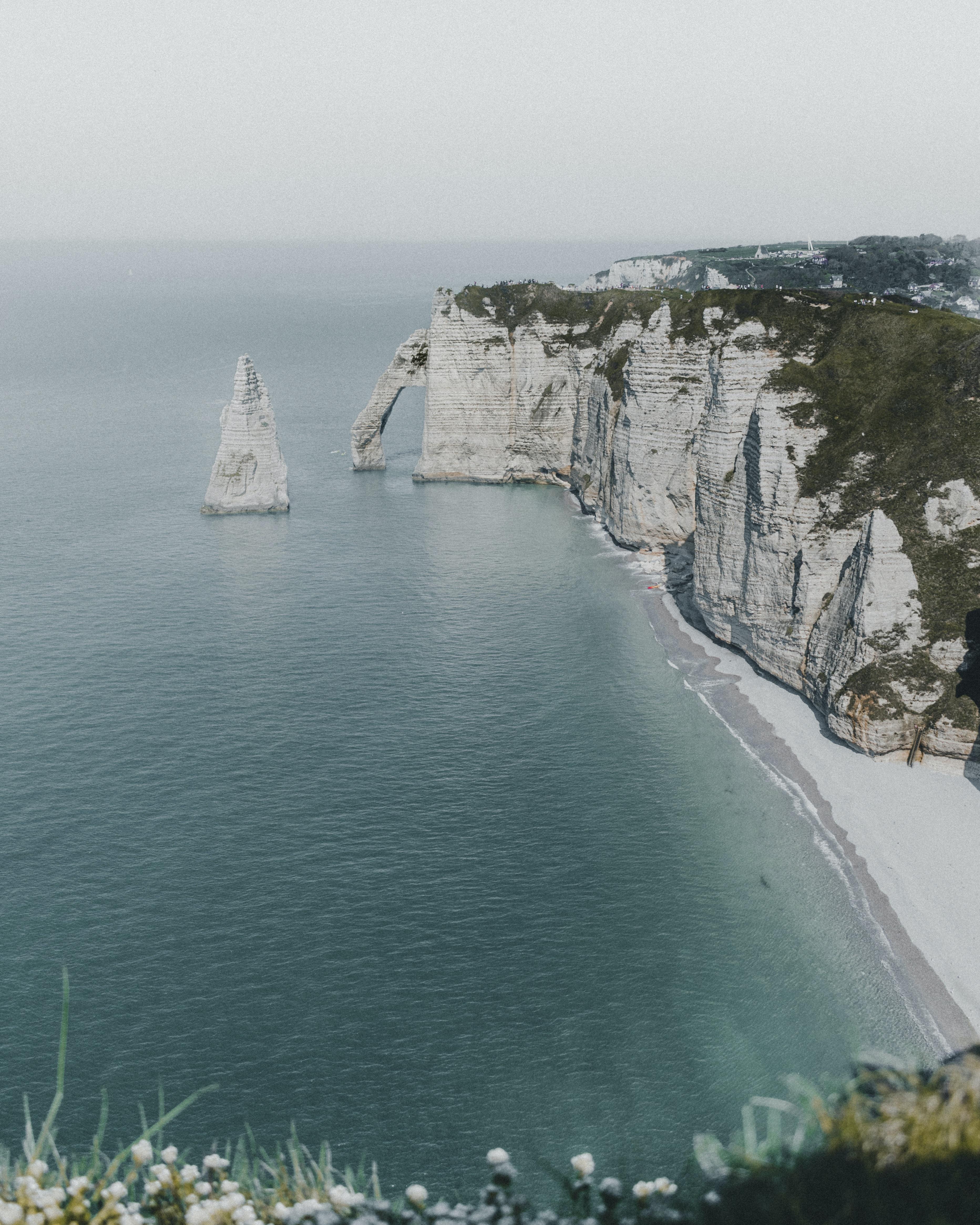 white mountain beside ocean during daytime