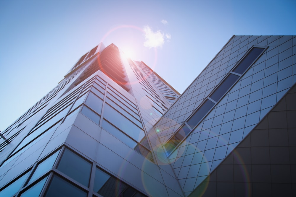 low-angle photography of blue glass walled buildings under blue and white sky