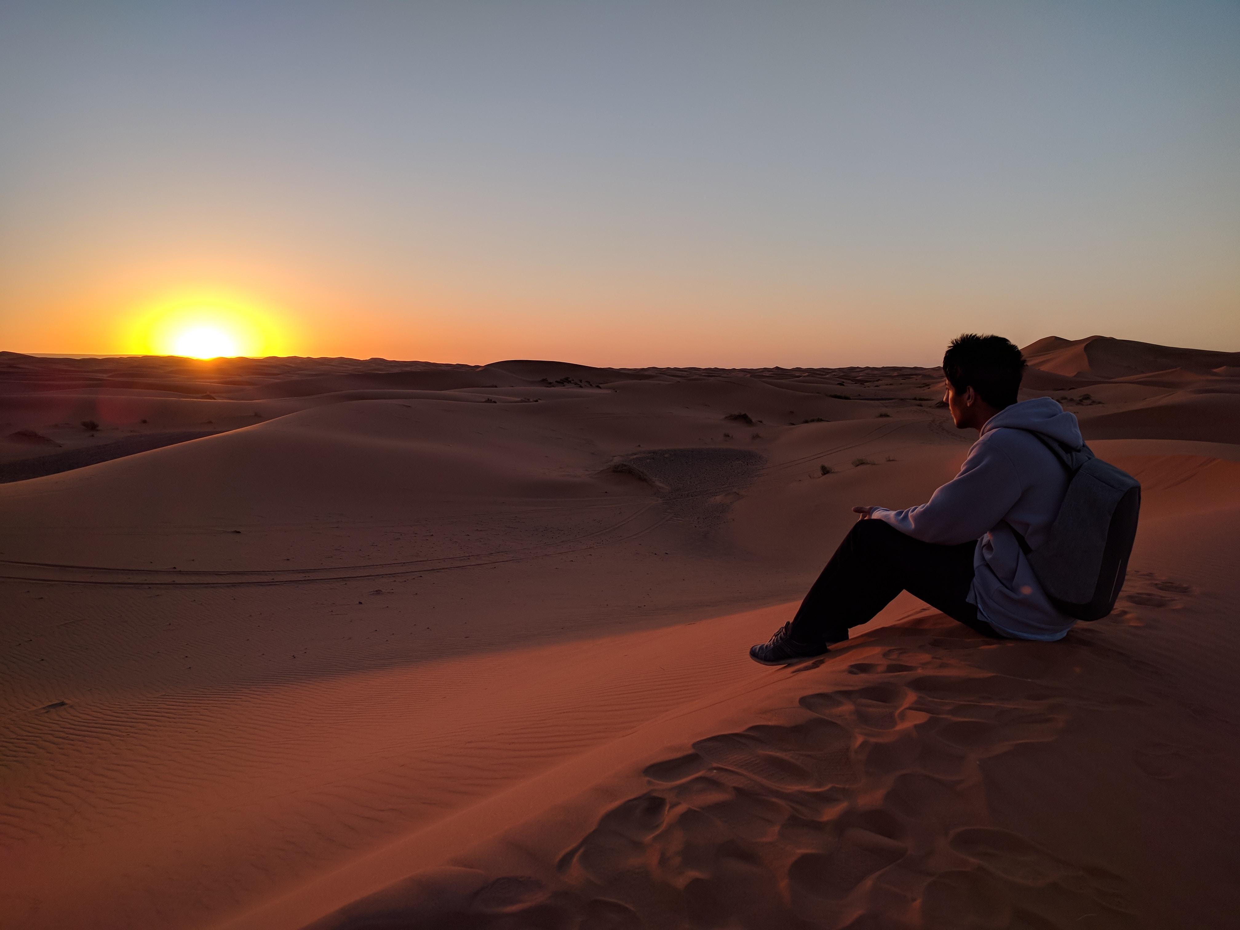 man sitting on desert dune