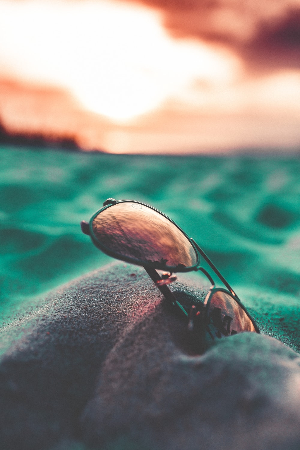 close up photography of black Aviator-style sunglasses on gray sand
